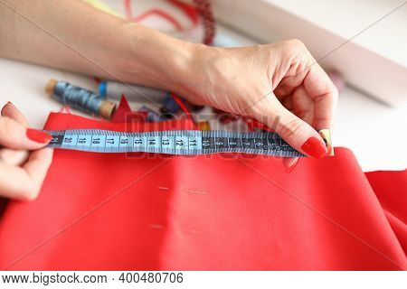 Close-up Of Female Dressmaker Using Blue Tape Measure For Work With Textile. Fabrics For Red Dress.