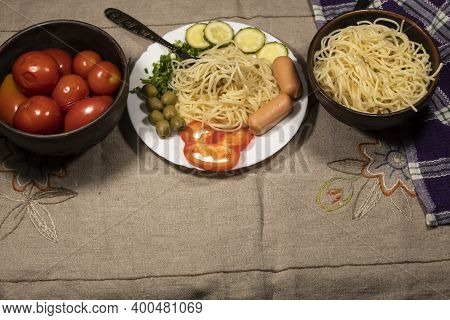 On The Table Is A Bowl Of Spaghetti And Salted Tomatoes. In The Middle Is A Plate Of Spaghetti, Saus