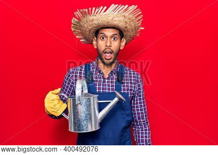 Young latin man wearing farmer hat and gloves holding watering can scared and amazed with open mouth for surprise, disbelief face
