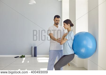 Physiotherapist Helping Young Woman Do Wall Squats With Fit Ball In Modern Clinic