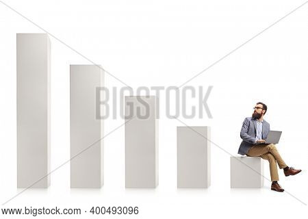 Professional man with a laptop sitting on a column and looking at rising column bars isolated on white background
