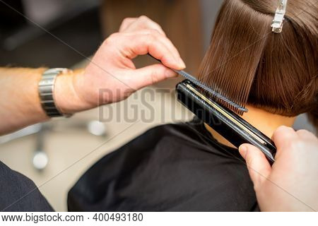 Close Up Of The Hairdresser Straightening The Short Hair Of A Female Client With A Hair Straightenin