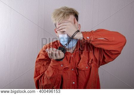 A Teenager In Handcuffs And A Medical Mask Holds His Head Against A Gray Background.headache For Juv