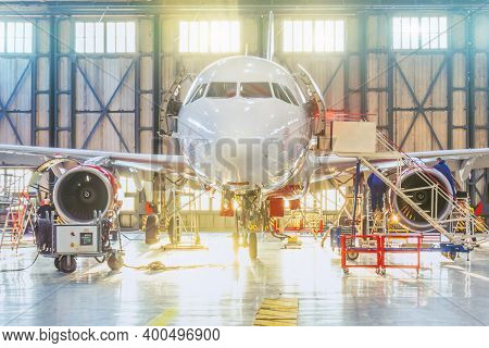 Aircraft Inside The Aviation Hangar, Maintenance Service. Airplane Mechanic Working Around. Bright L
