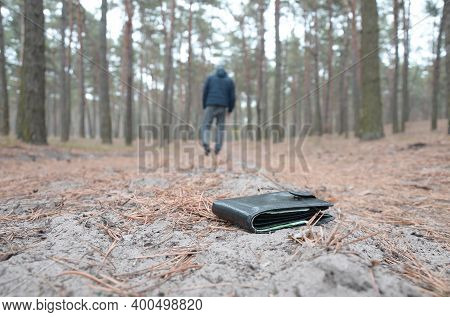 Young Man Loses His Purse With Euro Money Bills On Russian Autumn Fir Wood Path. Carelessness And Lo
