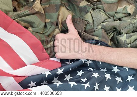 Hand Shows Thumbs Up On American Flag And Military Uniform
