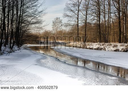 Frozen River In A Park With Trees Along The Banks