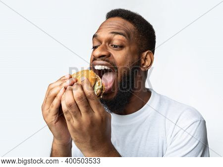 Hungry African Man Eating Burger Greedily Enjoying Unhealthy Fastfood Standing Over White Studio Bac