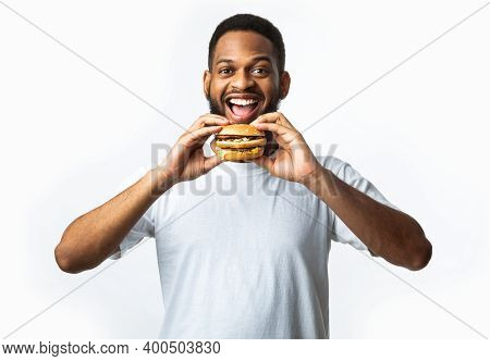 Hungry African Guy Biting Burger Eating Unhealthy Junk Food Standing Smiling To Camera Over White Ba