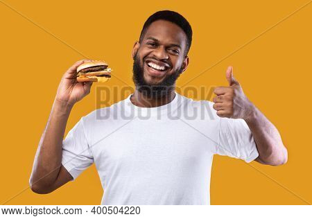 I Like Junk Food. African Guy Holding Burger Gesturing Thumbs Up Smiling To Camera Posing On Yellow