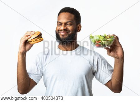 Hungry Black Guy Choosing Between Burger And Vegetable Salad Standing Over White Studio Background.