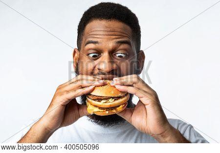 Funny Hungry African Guy Eating Burger Standing On White Studio Background. Black Man Enjoying Hambu