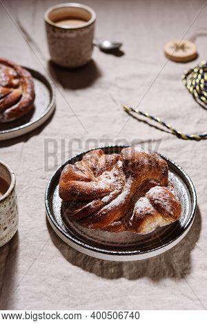 Cinnamon Swirl Brioche Or Cinnamon Roll Bun And Cups Of Cocoa On Greige Linen Tablecloth. Homemade B