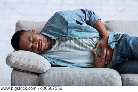 Stomachache. African Guy Suffering From Abdominal Pain Touching Aching Stomach Lying On Sofa At Home