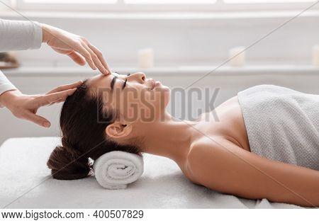 Attractive Korean Woman Enjoying Acupressure Face Massage Procedure At Beauty Salon, Lying On Spa Ta