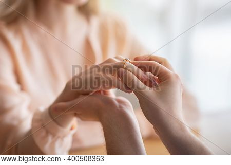 Closeup Of Young Man Putting Diamond Engagement Ring On His Girlfriends Finger, Making Marriage Prop