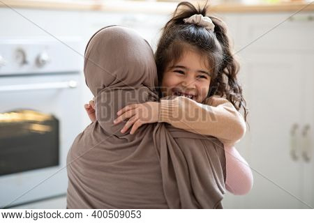 Cute Little Girl Hugging Her Muslim Mom In Headscarf And Smiling, Loving Family Bonding With Each Ot