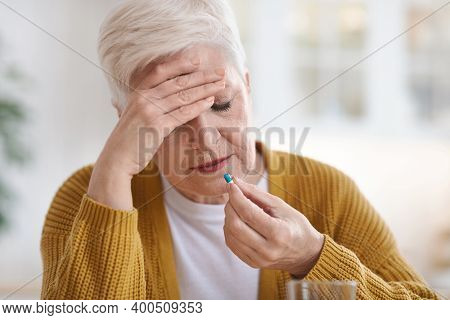 Upset Senior Woman Suffering From Headache, Touching Her Temples And Taking Pill, Kitchen Interior,
