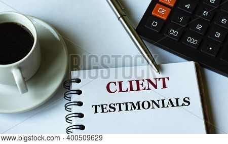 Client Testimonials - Words Written In A Notebook Against The Background Of A Calculator And A Cup O