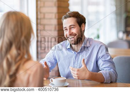 Happy Young Guy Talking To His Girlfriend While Having Coffee At Cafe. Millennial Couple On Romantic