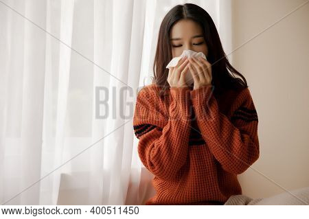 Young Asian Ill Woman With Handkerchief Coughing And Sneezing, Near Window At Home. Sick Girl Holdin