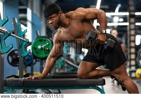 Hot African American Young Man Bodybuilder Lifting Barbell At Gym, Working On His Arms, Looking At C