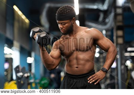 Biceps Workout Session. Handsome African American Shirtless Athlete Training Arms With Dumbbells At