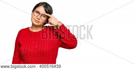 Young beautiful hispanic woman with short hair wearing casual sweater and glasses pointing unhappy to pimple on forehead, ugly infection of blackhead. acne and skin problem
