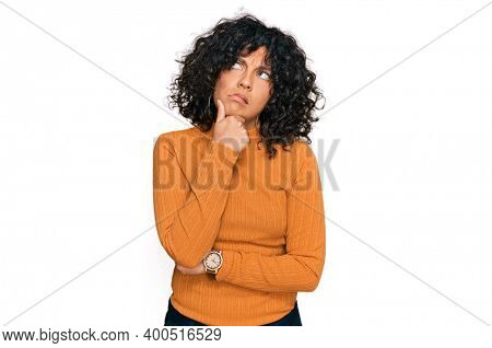Young hispanic woman wearing casual clothes thinking worried about a question, concerned and nervous with hand on chin
