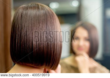 Short Hairstyle Of Woman While Looking In The Mirror At Hair Salon.