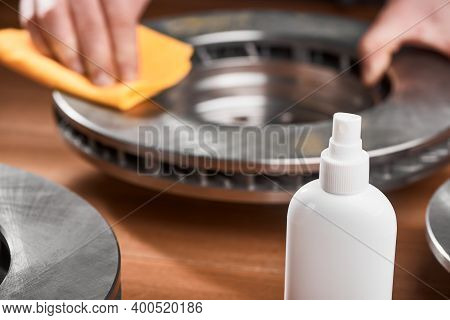 Close-up On An Anti-rust Spray And Man Cleaning A Brake Rotor In The Background