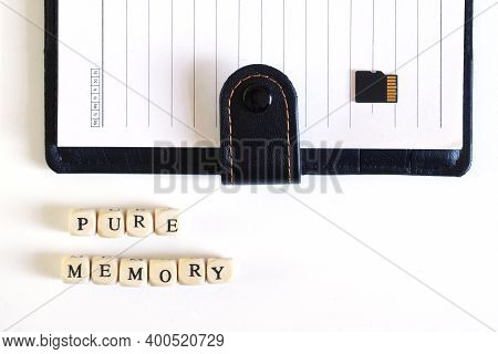 Pure Memory Lettering Next To An Open Blank Notebook And A Blank Micro Sd Memory Card. An Allegory O