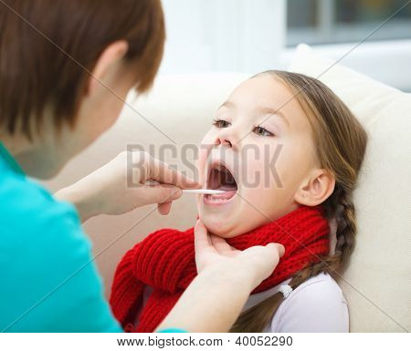 Doctor is examining a little girl, indoor shoot