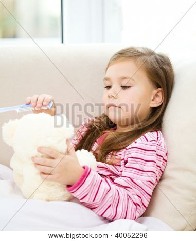 Little girl is brushing her teddy bear while laying in bed and wearing pajama, indoor shoot