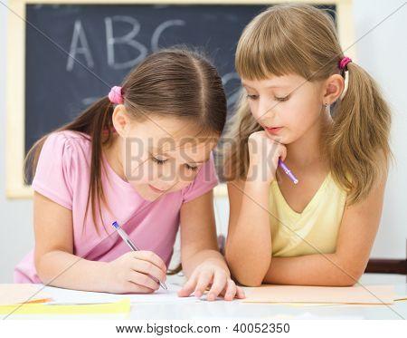 Cute little girl is writing using a pen in preschool