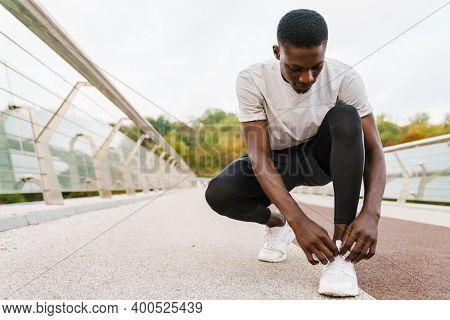 Sporty african man tying shoelace on bridge