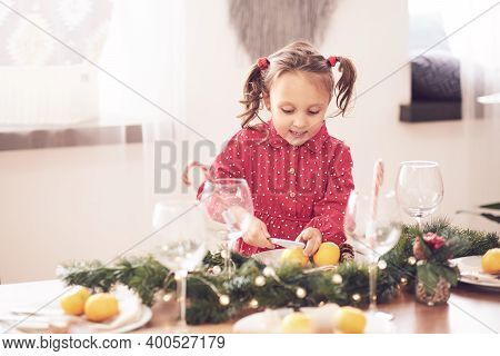 Cute Curly Toddler Girl Standing At A Christmas Dinner Table Settling The Dishes Preparing To Celebr