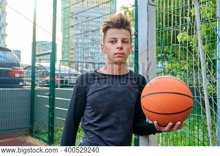 Guy Teenager With Basketball In His Hands, Outdoor Basketball City Court Background. Active Sports H