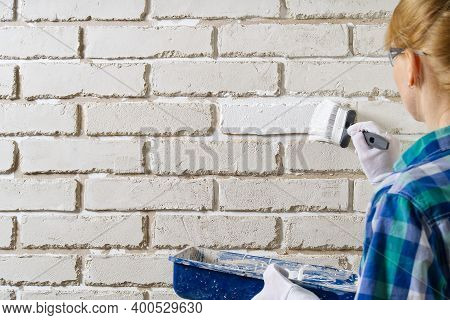 Diy Wall Repairing, Woman Painting A White Brick Wall With A Paint Brush