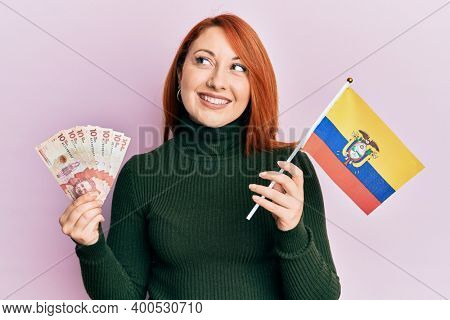 Beautiful redhead woman holding colombia flag and 10 colombian pesos banknotes smiling looking to the side and staring away thinking.