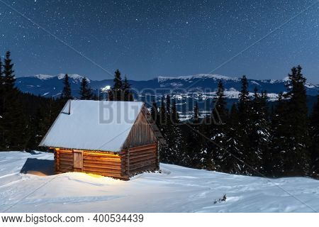 Fantastic winter landscape with wooden house in snowy mountains. Starry sky with Milky Way and snow covered hut. Christmas holiday and winter vacations concept