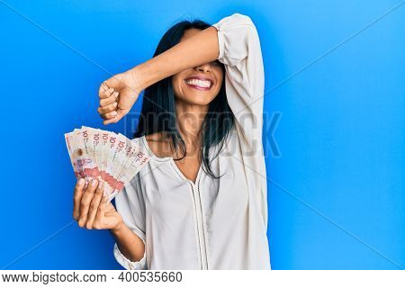 Young african american woman holding 10 colombian pesos banknotes smiling cheerful playing peek a boo with hands showing face. surprised and exited