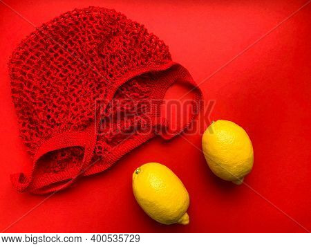 Red String Bag With Yellow Lemons. Vitamin C. Yellow And Red Color. Lemons In A Red String Bag On A