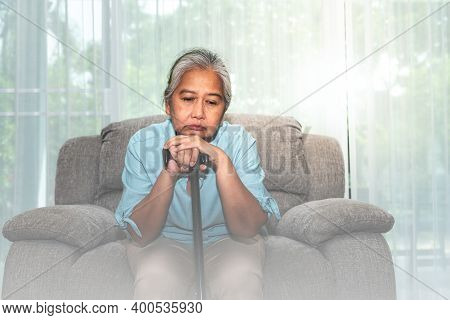 Portrait Images Of Asian Elderly Woman Holding The Cane To Support, Sitting Absent Lonely On The Sof