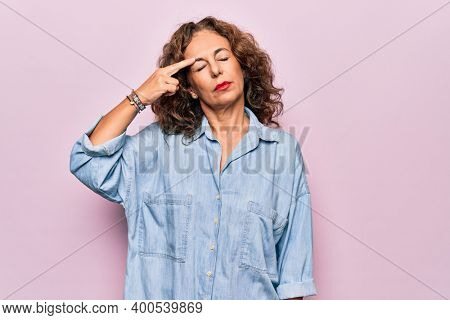 Middle age beautiful woman wearing casual denim shirt standing over pink background pointing unhappy to pimple on forehead, ugly infection of blackhead. Acne and skin problem