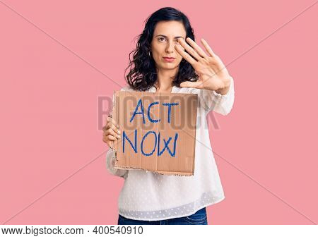 Young beautiful hispanic woman holding act now banner with open hand doing stop sign with serious and confident expression, defense gesture