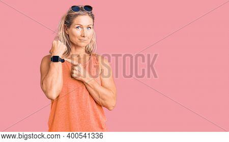 Middle age fit blonde woman wearing casual summer clothes and sunglasses in hurry pointing to watch time, impatience, looking at the camera with relaxed expression
