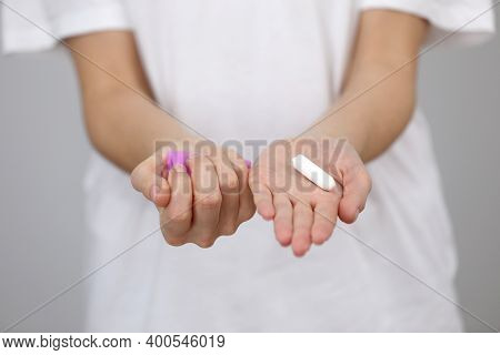 Close Up View Of Young Woman Making Choice Between Menstrual Cup And Tampon, On White Background. Gy