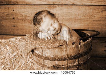 A newborn baby in a wooden bucket
