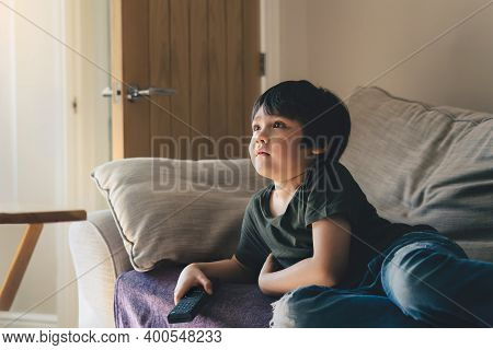 Cinematic Portrait Of Young Boy Lying On Sofa Watching Tv In Living Room, Kid Holding Remote Control